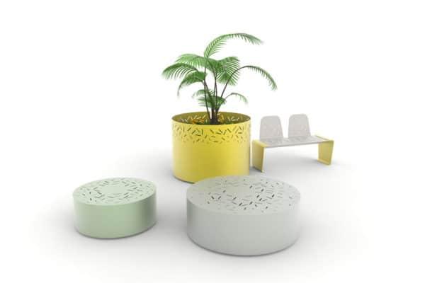 Un banc galet LUD vert et un banc galet XL LUD gris en premier-plan ; une jardinière XL LUD et un banc LUD avec deux dossiers jaunes en arrière-plan