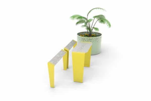 Une table bar LUD jaune avec deux assis-debout LUD jaune ; à l'arrière-plan, une jardinière XL LUD verte