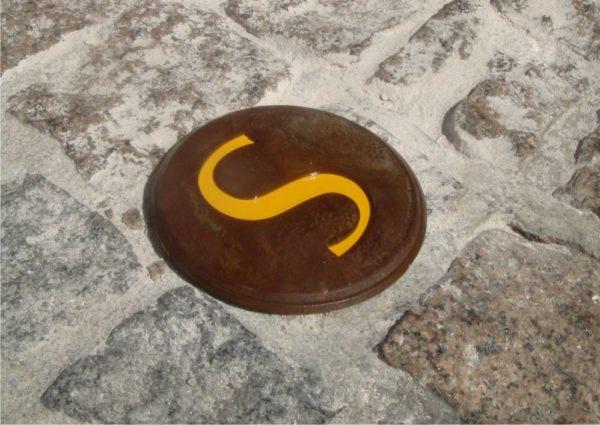 Une photographie d'un clou de jalonnement Icare incrusté verticalement dans des routes pavées