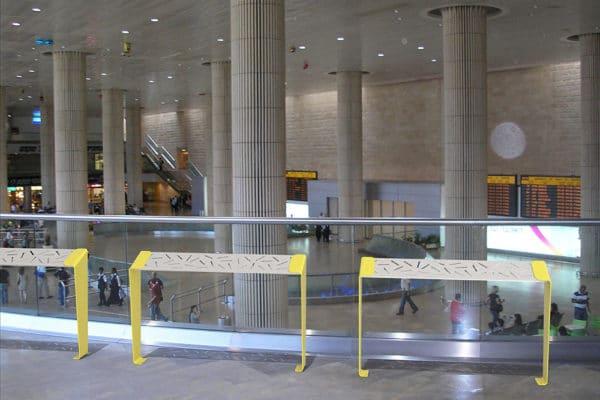 Trois assis-debout LUD jaunes incrustés sur le sol d'une gare, près de vitres