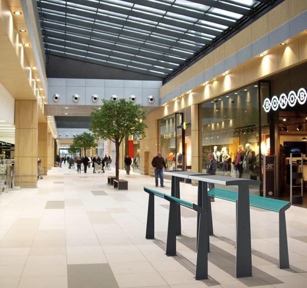 Deux tables bar TUB grises et quatre assis-debout TUB bleus incrustées dans une photographie prise dans un centre commercial