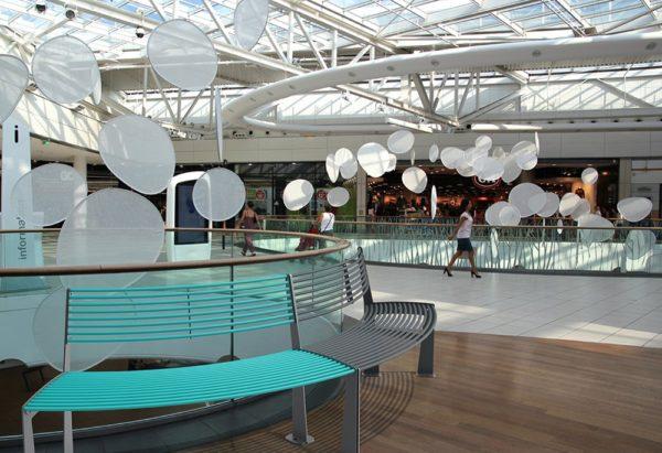 Deux bancs circulaires TUB, l'un bleu, l'autre gris, incrustés sur le parquet d'un centre commercial
