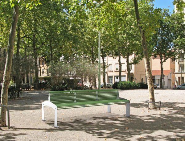 Un banc double TUB vert incrusté sur un sol dans un parc public