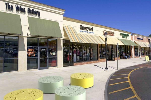Quatre bancs galet LUD, deux jaunes et deux verts, incrustés sur un sol en pierre, proches de devantures de magasin