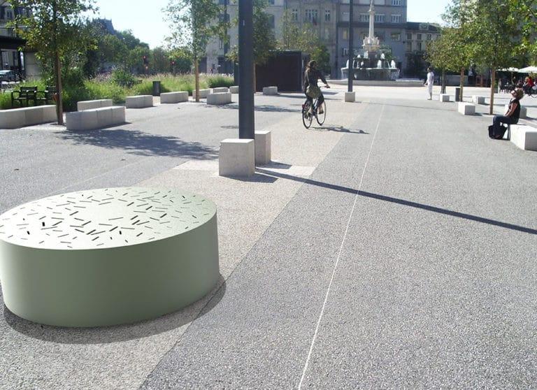 Un banc galet XL LUD vert incrusté sur un sol en béton