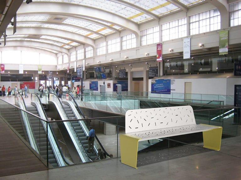 Un banc XL LUD jaune incrusté sur le sol d'une gare