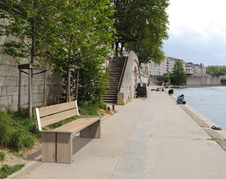 Un banc XL NUT incrusté sur un sol en pierre près d'un fleuve