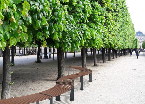 Cinq banquettes circulaires TUB incrustées sur le sol granuleux d'un parc public