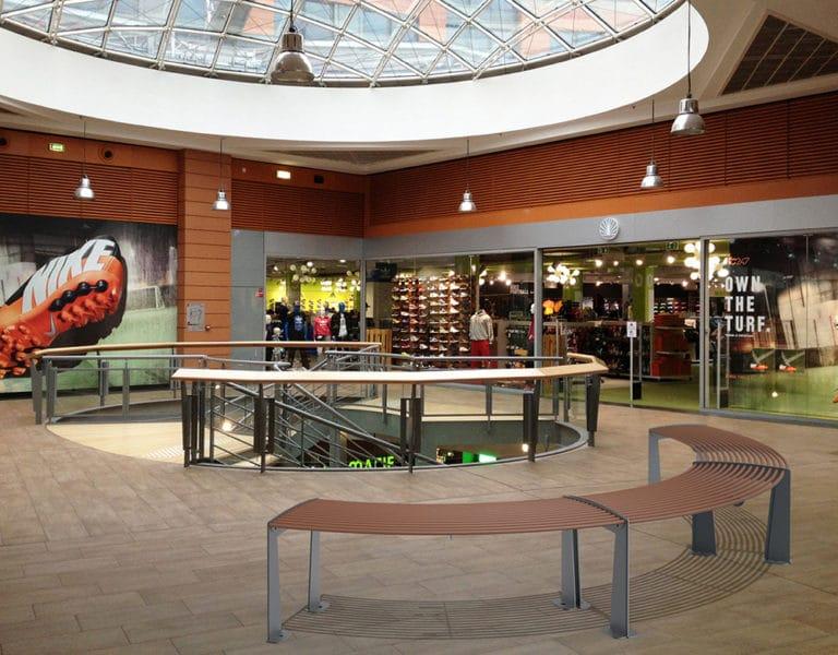 Trois banquettes circulaires TUB marron incrustées sur le sol d'un centre commercial