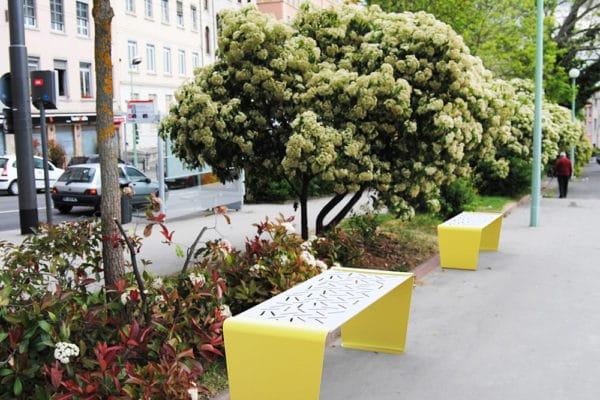 Deux banquettes LUD jaunes incrustées sur le sol d'une rue piétonne