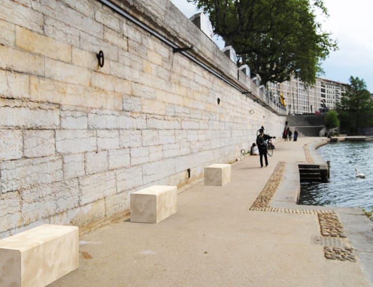 Trois banquettes en pierre naturelle sont disposées le long des quais près d'un fleuve