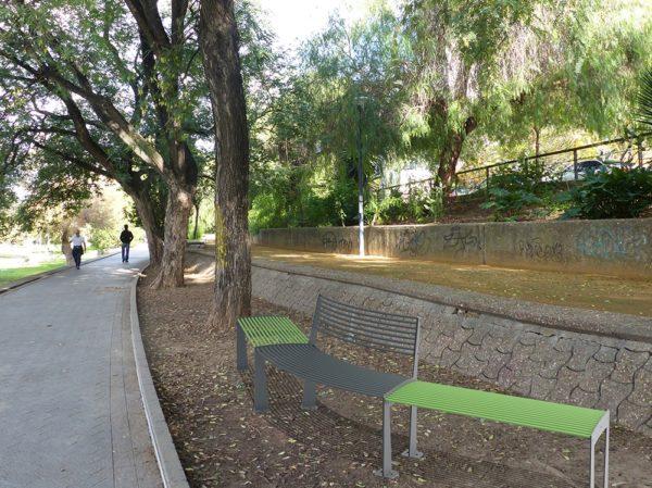 Deux banquettes TUB vertes entre un banc circulaire TUB gris incrustés sur de la terre dans un parc