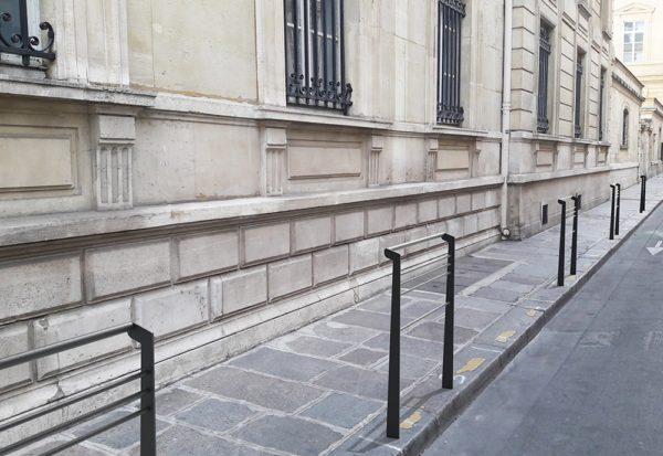 Cinq barrières TUB grises incrustées en bordure de trottoir dans une photographie