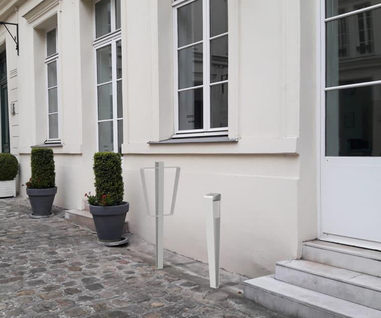 Une borne vélo et cendrier LUD gris incrustés sur le sol en pavés en pierre devant l'entrée d'un bâtiment