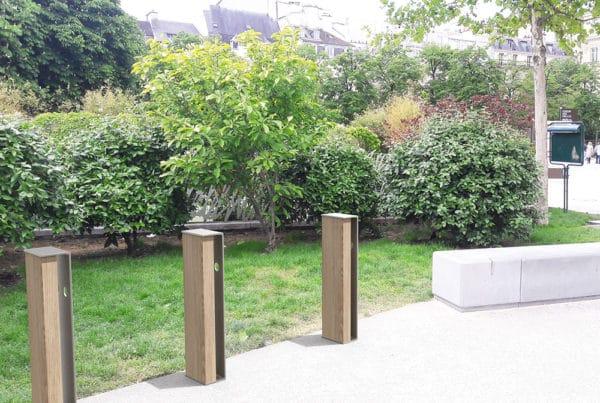 Trois bornes à vélo NUT incrustées sur un sol en pierre dans un petit parc public