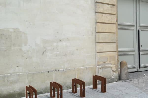Quatre bornes à vélo TUB marron incrustées dans une photographie sur un trottoir et près d'un mur