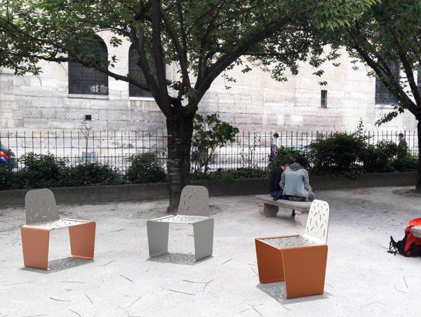 Trois chaises LUD, deux orange et une grise, incrustées sur le sol en pavés de pierre d'un parc