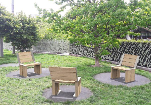Trois chaises NUT incrustées sur le sol dans un petit parc public