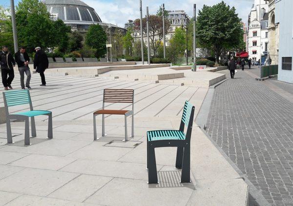 Trois chaises TUB (deux bleues et une marron) insérées dans une photographie d'une sorte de place urbaine