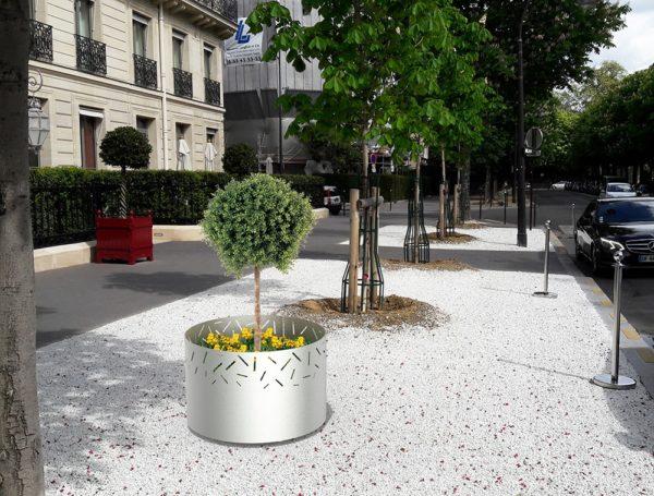 Une jardinière LUD grise incrustée sur un grand trottoir