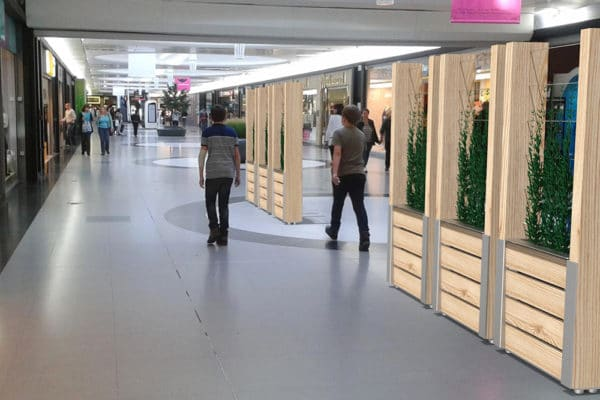 Six jardinières treillage NUT incrustées dans une photographie d'un intérieur de centre commercial