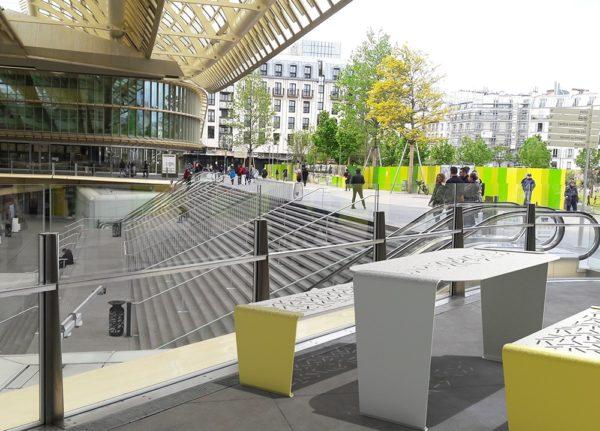 Une table LUD grise et deux banquettes LUD jaunes incrustées sur le sol d'une gare