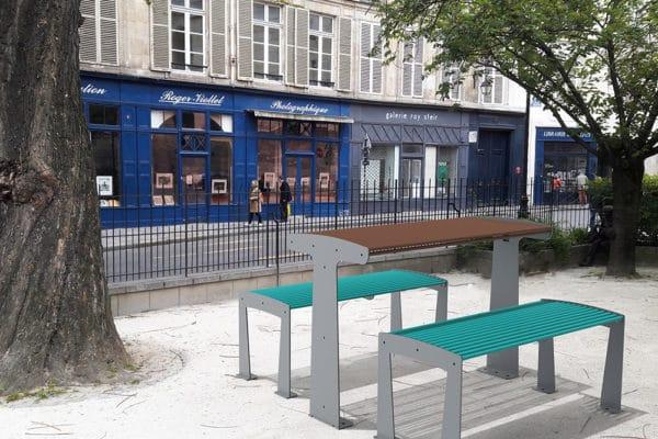Une table TUB marron et deux banquettes TUB bleues insérés dans une photographie de petit parc