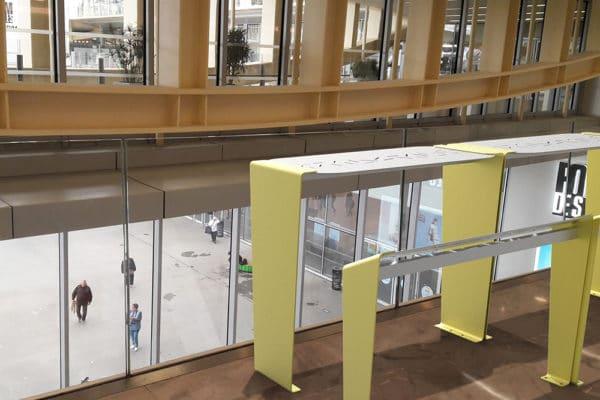 Deux tables bar et leurs assis-debout LUD jaunes incrustés sur le sol d'une gare, proche de vitres