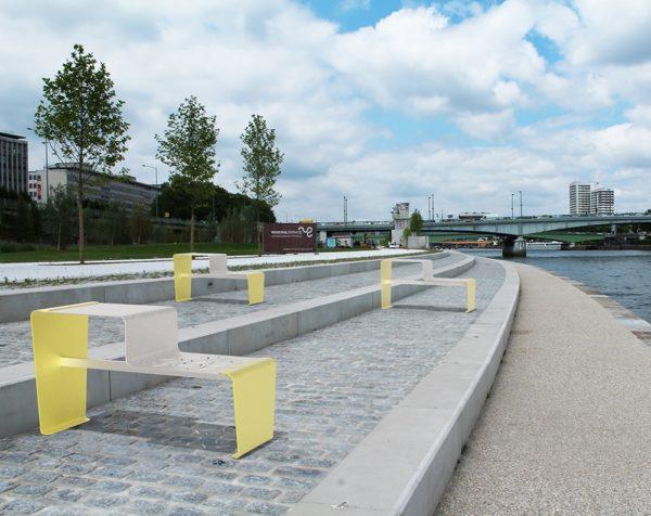 Trois tables gigogne LUD jaunes incrustées sur des pavés en pierre, près d'un fleuve