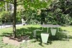 Une table pique-nique LUD verte incrustée sur une pelouse dans un parc