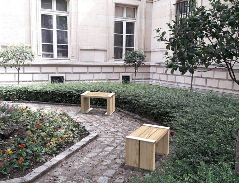 Deux tabourets NUT incrustés sur des pavés de pierre dans un petit jardin public