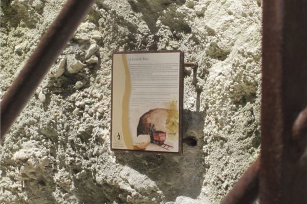 Une plaque murale Icare présentant le tunnel du Baou incrustée dans de la roche