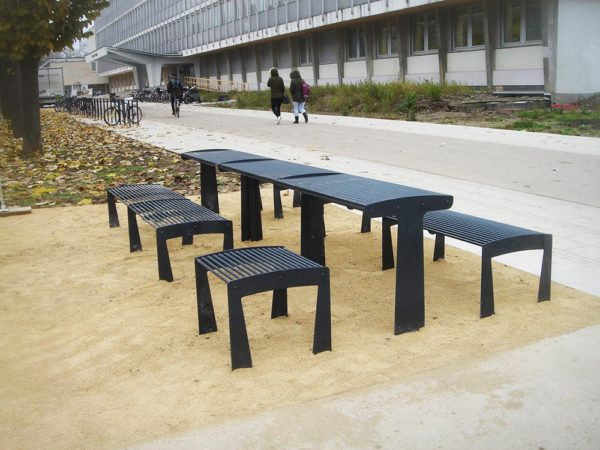 Une photographie de vraies tables TUB grises avec des tabourets et des banquettes TUB grises