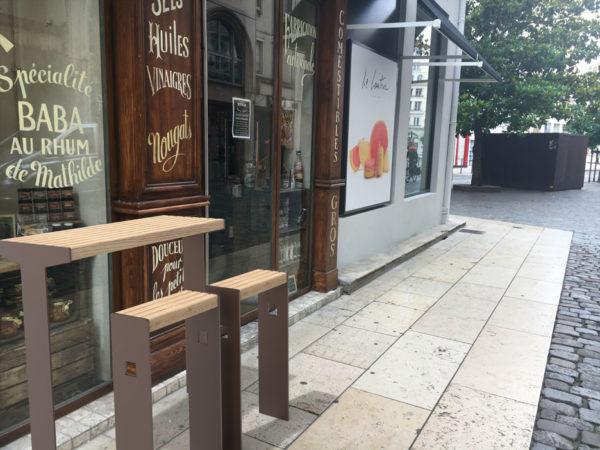 Insertion 3D d'une table bar avec ses assis-debout CUB marron sur la devanture d'un magasin
