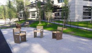 En premier plan, trois fauteuils CUB gris et marron ; en arrière-plan, deux fauteuils CUB gris et marron qui se font face